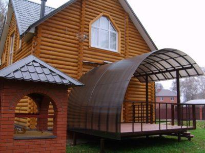 Навес над крыльцом, имеет полукруглую изящную форму и поликарбонат в качестве основного материала для создания конструкции